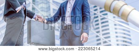Businessman transfer deal, business black briefcase exchange urban city background.handover of a suitcase in the hands of partners.