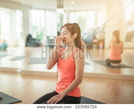 woman yogi practicing yoga, sitting in Padmasana, Lotus pose, using Alternate Nostril Breathing, nadi shodhana pranayama, working out,in yoga studio