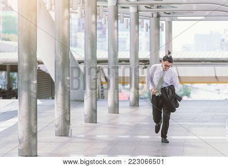 Stressed anxious businessman in a hurry and running, he is late for his business appointment and Wear a shirt while running.