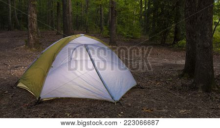 Nylon tent in a campsite as darkness is falling