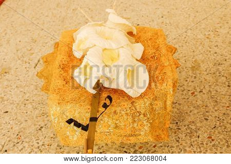 Close up of white and yellow Sandalwood flowers or artificial flowers in the golden tray with pedestal