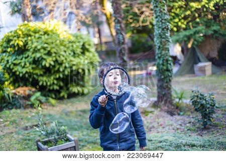 7-year-old Child Outdoors In The Garden In Winter Makes Big Soap Bubbles
