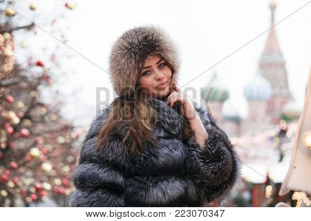 Portrait of a Young beautiful woman in blue fur coat, posing in winter Red Square in central Moscow