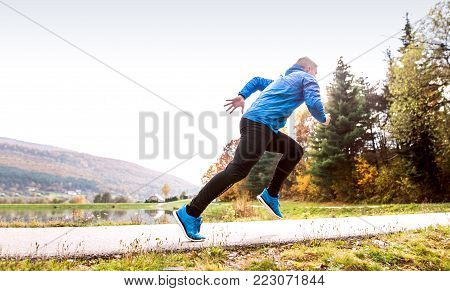 Young athlete in blue sports jacket at the lake running against colorful autumn nature.