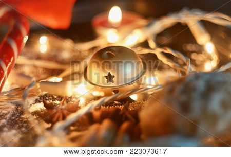 Smooth and calm colors. Jingle bell in the center of the photo. Candles in the background complement the photo with light, as well as a candy that gives a warm reddish hue to the whole picture.