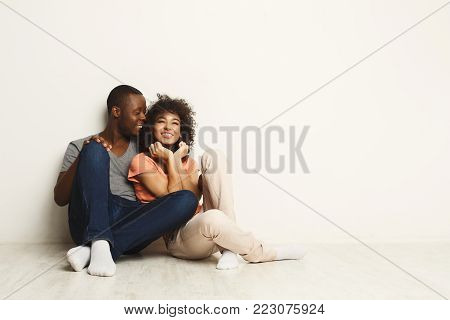 Happy african-american family couple hugging and looking up, sitting on floor in new apartment, dreaming about future, copy space, isolated