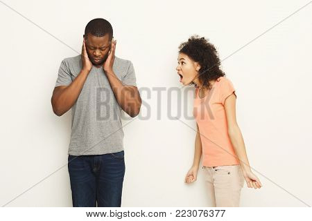 Black couple arguing. Angry african-american women shouting at man who covering ears with hands at white studio background, copy space. Break up or divorce, family misunderstanding concept, , isolated