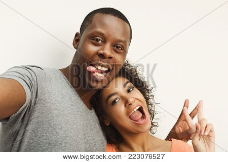 Couple selfie. Studio shot of casual african-american couple grimacing and showing victory sign on white studio background, copy space, isolated