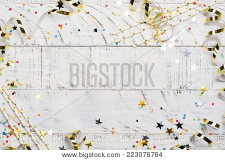 Bright festive carnival background with hats, streamers, confetti and balloons on white wooden background. Copy space
