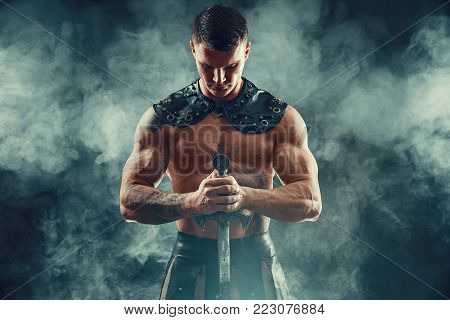 Portrait of handsome muscular gladiator with sword. Studio shot. Smoke on background.