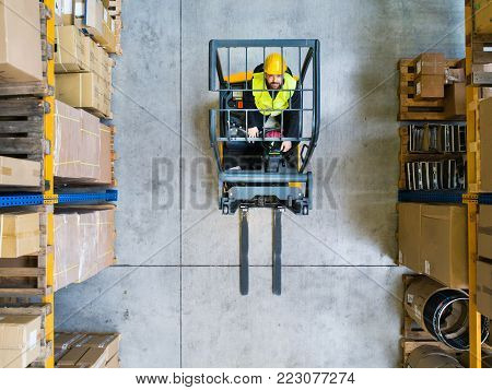 Man forklift driver working in a warehouse. Aerial view.