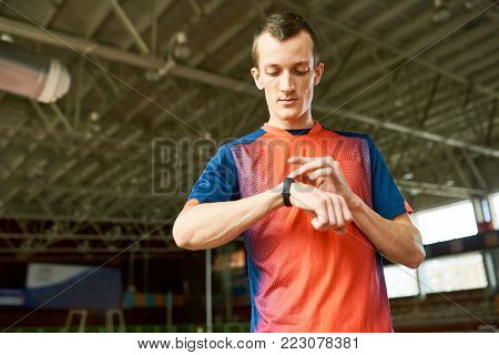 Waist up  portrait of modern young sportsman checking fitness activity tracker standing  in indoor stadium, copy space