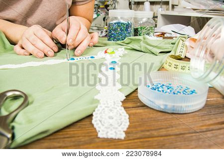 A Woman Is Making Jewelry, A Home Workshop. Female Hands That Create An Accessory With Beads And Rib