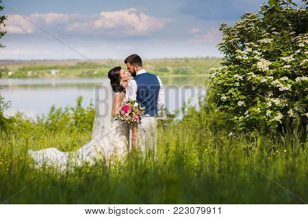 Amazing just married couple in the landcape with water and blossom bushes outroors. Bride and groom look at each other