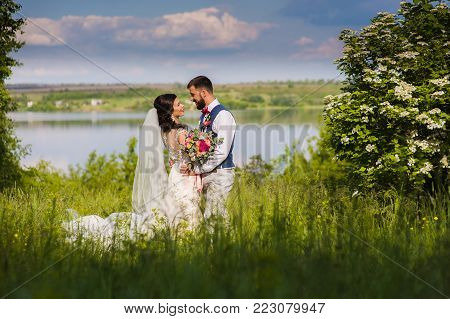 Amazing just married couple in the landcape with water and blossom bushes outroors