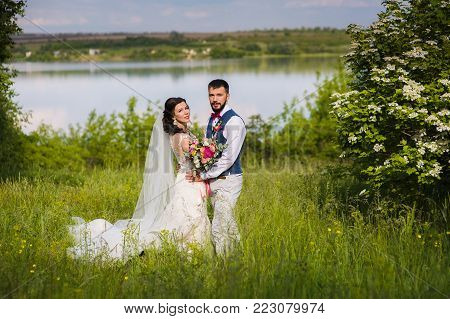 Amazing just married couple in the landcape with water and blossom bushes outroors. Look at the camera