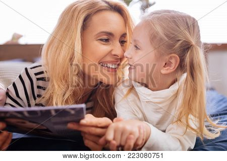 I cherish you. Loving joyful blond mother and her little daughter smiling and reading a magazine and mom caressing her