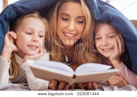 Reading. Devoted content blond mother and her little daughters smiling and reading a book while lying on the couch