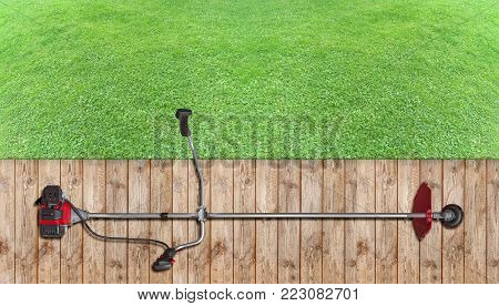 Whole trimmer lawnmower red for grass like garden machine on wooden terrace with green grass