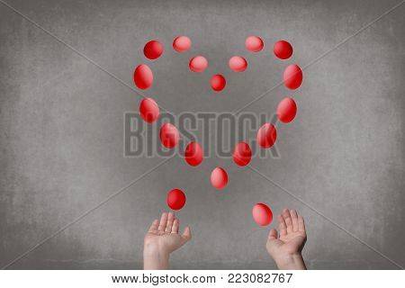 Female hands juggle eggs in the form of Valentine's heart . Food and relations сoncept
