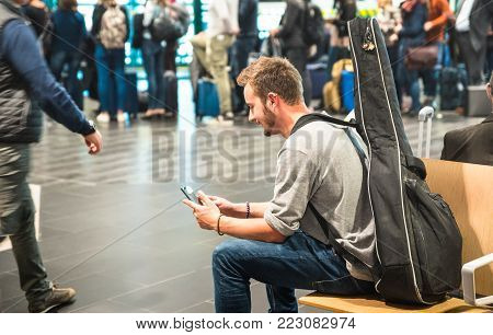 Hipster man at international airport using mobile smart phone - Wanderer person at terminal gate waiting for airplane - Wanderlust travel trip concept with guy and guitar backpack - Focus on face