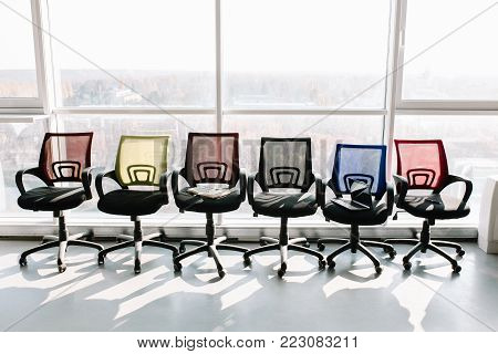 Six Office chairs with colorful backs. Standing at the big window.