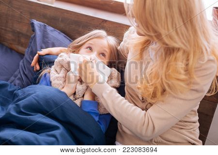 Blowing nose. Devoted worried blond mother holding a napkin and helping her ill daughter blow her nose while her kid lying in bed and looking at her