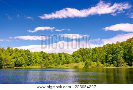 mountain lake among the green forest in picturesque springtime landscape. reflection in crystal clear water. beautiful weather with blue sky and some clouds