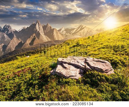 composite of meadow in rocky mountains at sunset. beautiful unrealistic landscape in summertime