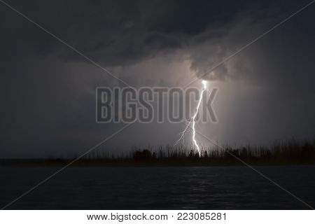 view of lightning over the lake, lightning strikes the ground