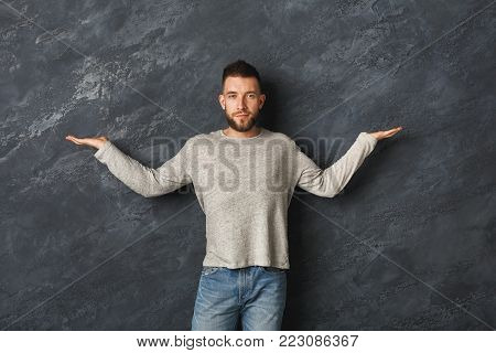 Handsome man keeping open hands on the sides, holding virtual objects or pondering on grey studio background, copy space. Commercial advertisement or pros and cons concept