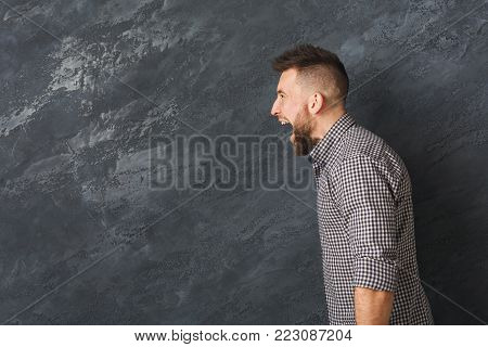 Man cry out in despair and shock. Expressing strong emotions, anger at grey background, studio shot, side view