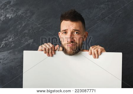 Handsome sad man posing and holding white pape with copy space for commercial advertising at gray studio background
