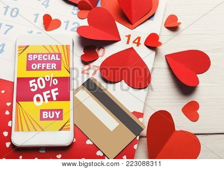 Valentine day online shopping and internet sales. Smartphone with discount offer on screen and credit card for payment at calendar and peper hearts background