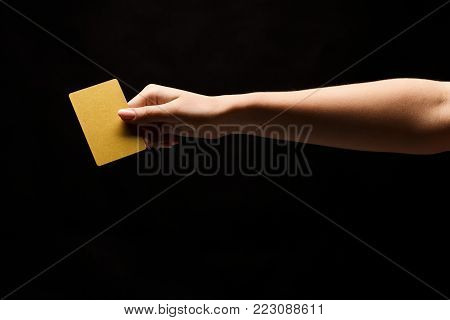 Female hand holding blank plastic credit card or business card on black isolated studio background. Banking services and acquaintance concept, copy space, cutout, low key
