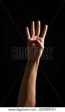 Male hand showing four fingers, number four isolated at black background. Counting, gesturing, enumeration concept, cutout, copy space