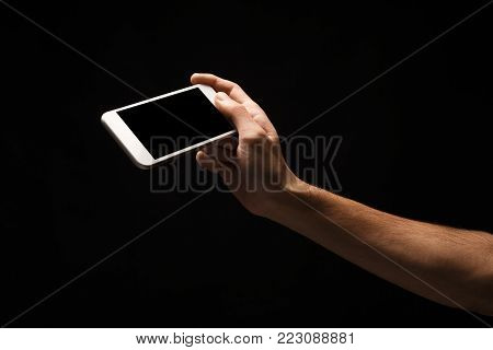 Male hand holding mobile smartphone with blank screen, isolated on black background. Copy space for advertisement of mobile app, mockup