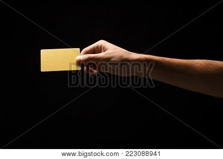 Male hand holding blank plastic credit card or business card on black isolated studio background. Banking services and acquaintance concept, copy space, cutout, low key