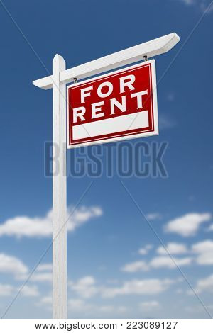 Right Facing For Rent Real Estate Sign on a Blue Sky with Clouds.