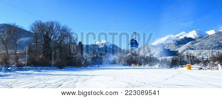 Bansko ski resort panorama with ski lift cabin, slope and snow mountains, Bulgaria