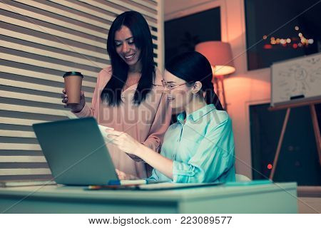 Pleasant supervisor. Upbeat pretty woman sitting at the table in the office and showing the printout with results of her work to her boss holding a cup of coffee