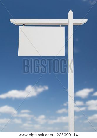 Blank Real Estate Sign Over A Blue Sky with Clouds.