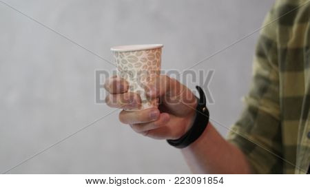 Man holding white cup then it changed to paper cup for coffee. A man is holding a brown paper cup. Man holding blank cup, close up.