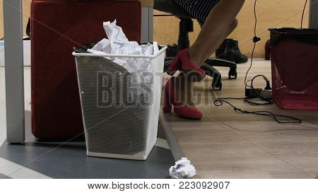 Trash bin - basket full of wastepaper in office. Man throws away paper documents. Paper throw in the trash.