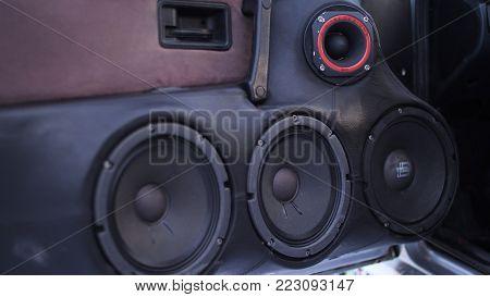 Car audio system close up honeycomb in front door panel, Car radio speaker. Music speakers in the doors of the car.