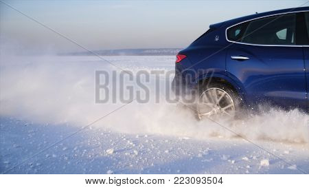 Car with winter tyres installed on light alloy wheels in snowy outdoors road. A car driving down a snowy road during winter. Car drives on a snowy road.