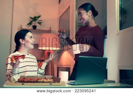 Quality time. Two pleasant female best friends having a sleepover party and talking to each other while eating pizza and drinking tea