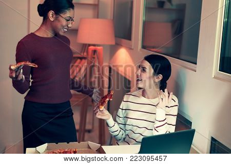 Precious moments. Two cheerful female best friends having a conversation and eating pizza while having a small party