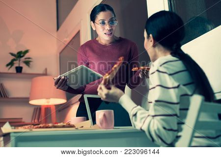 Informal atmosphere. Two pleasant young women discussing latest news at work, eating pizza and drinking tea while one of the woman having incredulous look