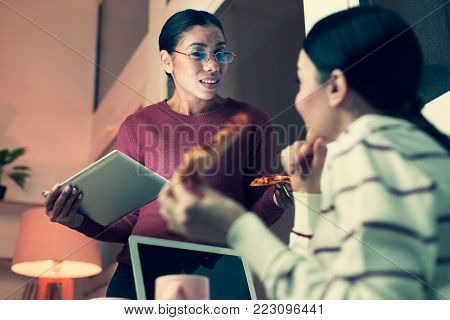 Unbelievable news. Charming young female colleagues chatting and sharing gossips during the break at work while eating pizza